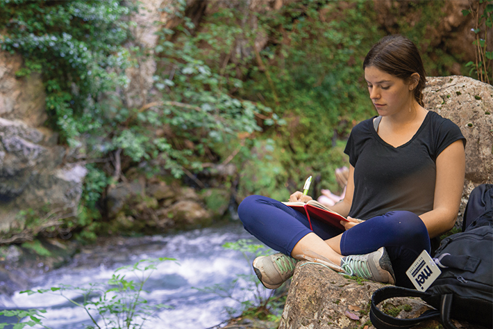 Student studying next to raging river